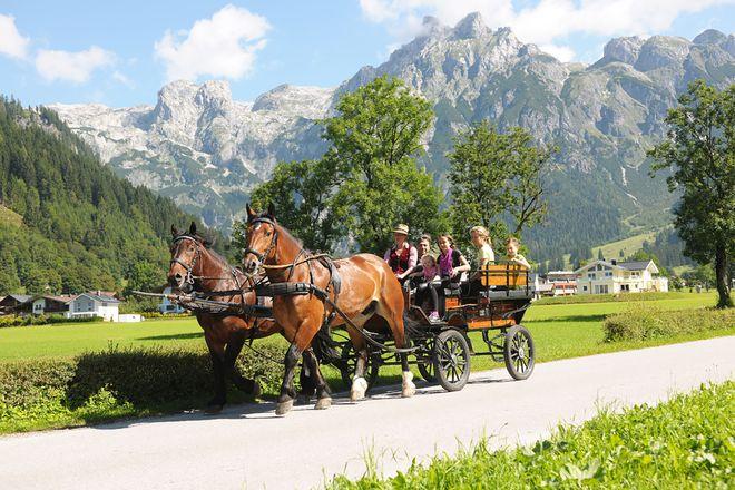 Entspannt: Mit der Pferdekutsche geht es vorbei an sagenhaftem Alpenpanorama.