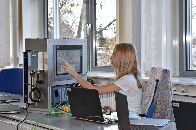 Alles unter Kontrolle: Eine Berufseinsteigerin eignet sich technische Fertigkeiten an einer Automatisierungssteuerung an.